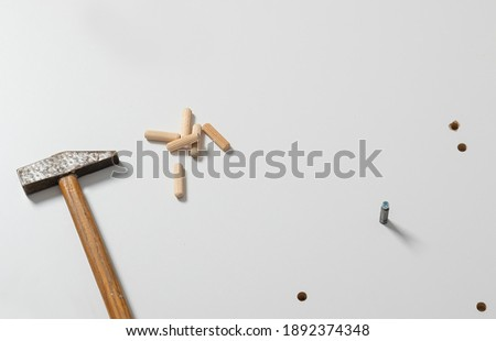 old hammer and wooden pegs on a light board. Furniture assembly preparation   Stock photo ©