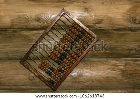 Old hand abacus hanging on a nail on the wall of wooden logs. #1062618743
