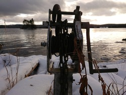 Old hand crank winch with a view a winter day