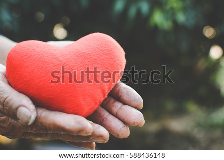 Old hand holding red heart shape vintage tone #588436148