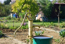 old hand pump at the well in the garden, saving water in times of drought