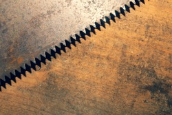Old hand saw on a dirty wooden background. working area with hand tool. carpentry instrument. manual labor concept