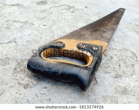 Old Hand Saw with wooden handle on cement ground for sawing boards, plywood and other materials. Tool fitter, carpenter. Saw for construction and repair, needlework.