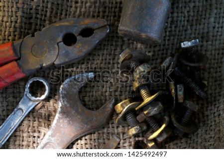 old hand tool, craftsman tool, top view hand tool with nut, wrench and pliers (selective focus)