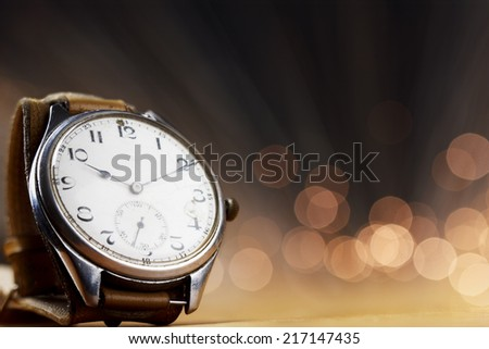 Old hand watch with bokeh background.