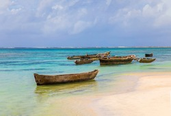 old handmade african  dhow fishing wooden boat anchored in the ocean in sunny weather