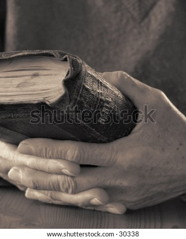 Old hands holding worn Bible