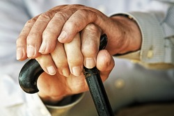 Old hands resting on a walking stick
