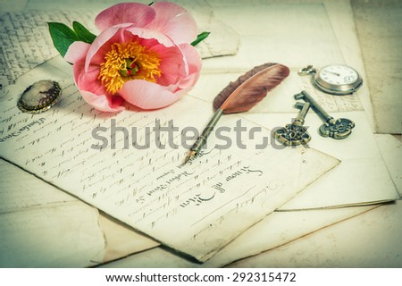 Old handwritings, antique feather pen, keys, pocket watch and pink peony flower. Sentimental vintage background. Retro style toned picture