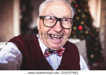 Old happy man taking selfie in front of a Christmas tree. Smiling, depth of field