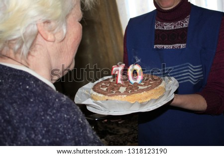 Old Happy Woman Blowing Out Candles On A Birthday Cake 70 Years