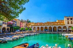 Old harbour Porto Vecchio with motor boats on turquoise water, green trees and traditional buildings in historical centre of Desenzano del Garda town, blue sky background, Lombardy, Northern Italy