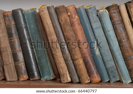 Old hardcover books on bookshelf