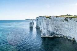 Old Harry Rocks chalk formations, view at Handfast Point, Dorset, southern England. Huge wall of white chalk cliffs with stumps and caves, tourist destination coastal view by the sea in south UK