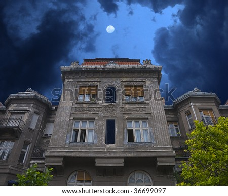 Old haunted house. Stormy clouds and moon can be seen behind it.