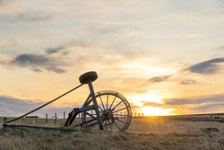Old Haymaking Machine (tractor) on grass field sunset time