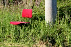 Old heavily used office chair with dilapidated red fabric mounted on rusted metal pole left in family house backyard next to concrete utility pole surrounded with overgrown uncut grass on warm sunny
