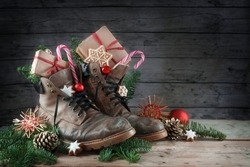 Old hiking boots filled with sweets,  and Christmas decoration on Nicholas day, or German Nikolaus Tag, 6th December  tradition to put the shoes outside, rustic wooden background, copy space, selectiv
