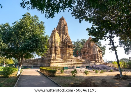 Old Hindu temple, built by Chandela Rajputs, at Western site in India's Khajuraho framed by trees. White grey for the younger and older beige structure against blue skies over green grass. #608461193