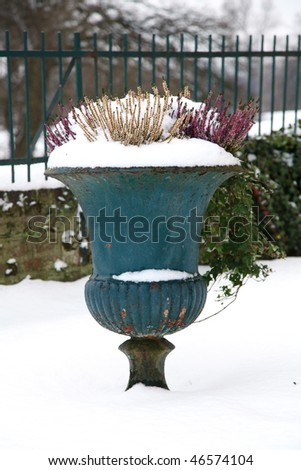 Old historic amphora in snow, germany, castle garden
