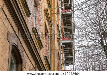 Old historic building facade under reconstruction with scaffolding