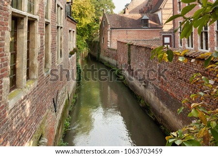 Old historic canal in Groot Begijnhof of Leuven. Is a well preserved beguinage and completely restored historical quarter containing a dozen streets in the south of downtown Leuven, Belgium. #1063703459