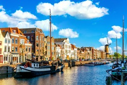 Old historic district Delfshaven with wildmill and houseboats in Rotterdam, South Holland, The Netherlands. Summer sunny day