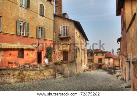 Old historic multicolored houses and paved street in town of Saluzzo, northern Italy.