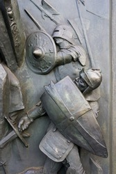 Old historical relief made of bronze - medieval warfare and battlefield. Warrior holds shield and swords. Defence and attack of knight during battle, combat and fight