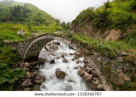 Old historical stone bridge on river under the fog at black sea region of Turkey. Historical Ottoman bridge Taskopru in Senyuva, Cinciva in Armenian, over the Firtina river near Camlihemsin in Rize pr
