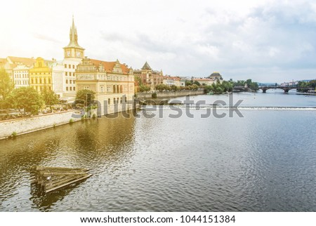 Old historical town Prague with Vltava river from Charles bridge, Czech republic. Travel destination. Yellow sun rays. #1044151384