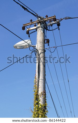 Old holder of the electrical installation with lighting against the sky - vertical
