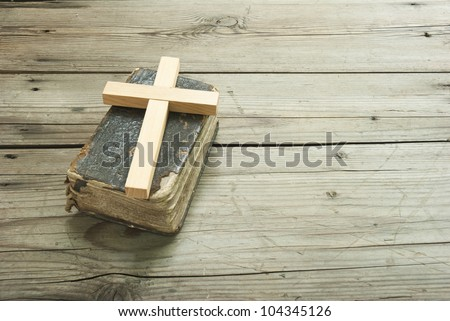 old holy bible and purity wood cross on rustic wooden table