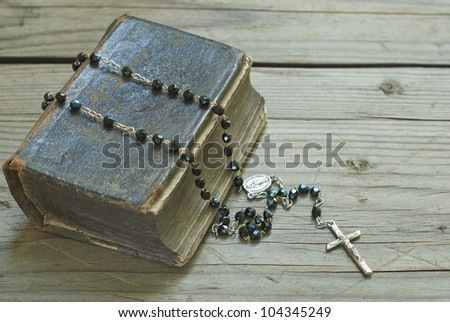 old holy bible and rosary beads on rustic wooden table