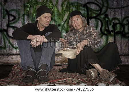 old homeless couple begging for alms - stock photo