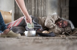 Old homeless man with gray beard and grey hair with wearing sweater and blanket sleeping the sidewalk and street walkway. Hand of kind woman giving banknote and donate money to poor man beggar.