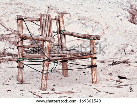 Old homemade bamboo chair on a deserted beach