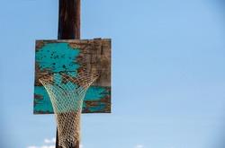 Old homemade wooden basketball hoop against the sky.