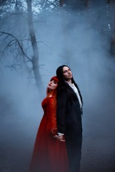 Old horror film style grain added. Gothic couple standing in fog. vampire man prince in black tailcoat embraces seduces woman. red medieval dress. Girl princess long hair. Mystical dark tree nature