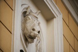 Old horse head sculpture made of stone at entrance of a house