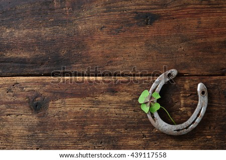 Old horse shoe with clover leaf on rustic wooden background #439117558