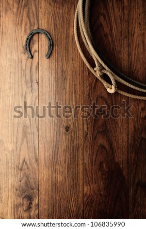 Old horseshoe and authentic American West rodeo cowboy lasso lariat hanging on an antique wood barn wall as a vintage Western background