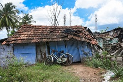 Old house or vintage abandoned house made with clay tiles and tin sheets in rural village, Tamil Nadu South India.