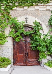 Old house wall with wooden door and green vine as a decorative plant, vertical background photo texture