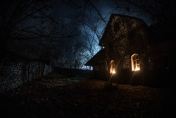 Old house with a Ghost in the forest at night or Abandoned Haunted Horror House in fog. Old mystic building in dead tree forest. Trees at night with moon. Surreal lights. Horror Halloween concept