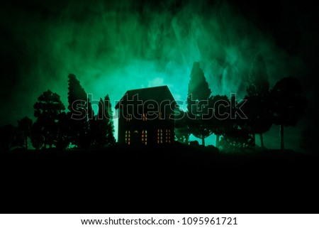 Stock Photo Old house with a Ghost in the forest at night or Abandoned Haunted Horror House in fog. Old mystic building in dead tree forest. Trees at night with moon. Surreal lights. Horror Halloween concept