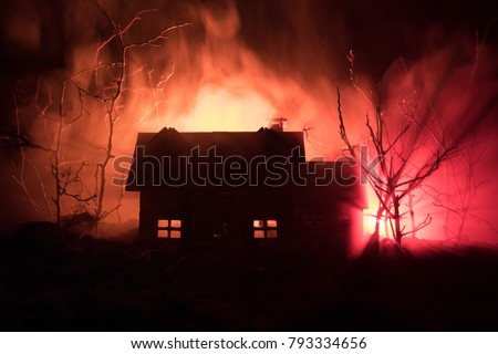 Stock Photo Old house with a Ghost in the forest at night or Abandoned Haunted Horror House in fog. Old mystic building in dead tree forest. Horror Halloween concept.