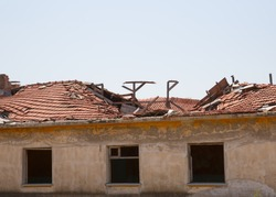 Old house with destroyed tiled roof