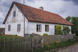 Old house with red tiled roof in a small village in Masuria region of Poland