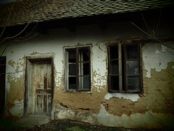 Old house with windows and a door. Collapsing rural house. The concept of urbanization and oblivion of the motherland. Abandoned house. Broken glass in the window and falling plaster. Serbia. Balkans.